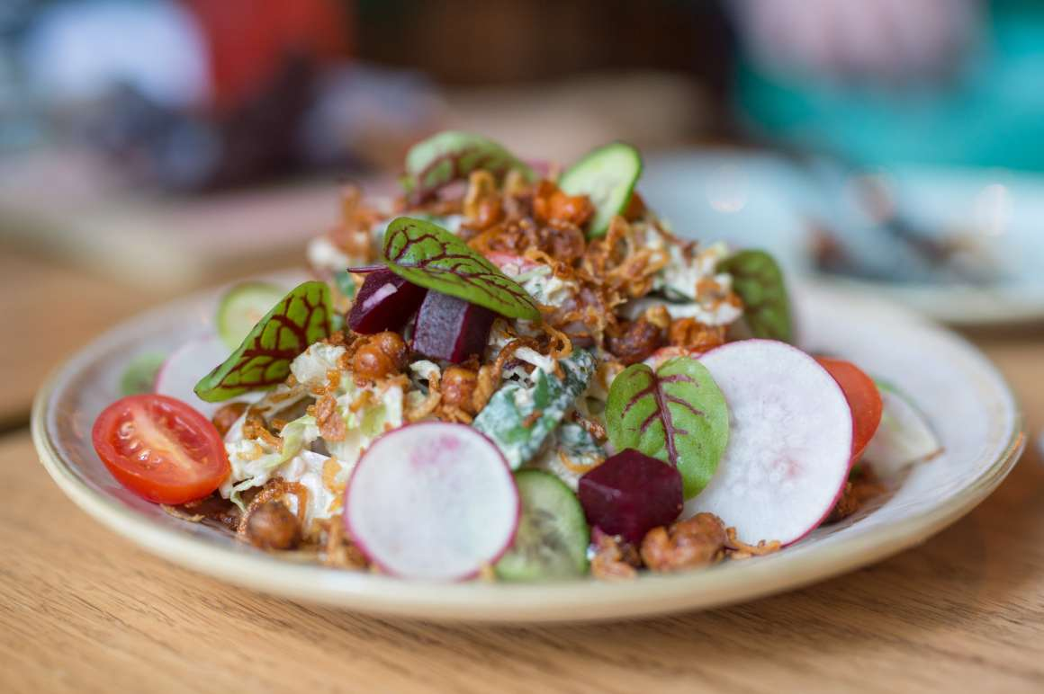 A picture of Reyna Salad from The Assembly Chef's Hall. Includes beet, cucumber, avocado, fennel, radish, tomato, quinoa, purple kale, fried chickpeas, crispy shallot, and serrano tahini dressing.