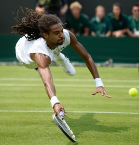 LONDON, ENGLAND - JUNE 26:  Dustin Brown of Germany dives to return a shot during his Gentlemen's Singles second round match against Lleyton Hewitt of Australia on day three of the Wimbledon Lawn Tennis Championships at the All England Lawn Tennis and Croquet Club on June 26, 2013 in London, England.  (Photo by Dennis Grombkowski/Getty Images)
