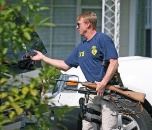 An ATF agent puts a pair of rifles taken from Larry McCoy's car in the back of an SUV Thursday Aug. 13, 2009. Federal agents and Mobile police raided Lary's Gun Shop, which McCoy owns and operates, on Pleasant Valley Road Thursday morning. Law enforcement officers took McCoy into custody shortly before 10 and seized a handgun and a pair of rifles from his vehicle. (Press-Register, Bill Starling) METRO