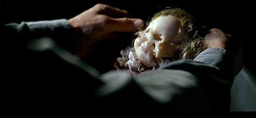 David finds Emily's doll completely defaced in a garbage can. The mutilation represents what the programming in the cave did to Emily's mind.
