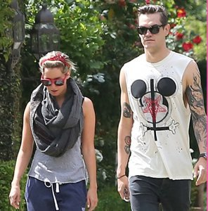 Speaking of former Disney child stars, here's Ashley Tisdale and her boyfriend who is wearing a t-shirt that features a Mickey Mouse head, an inverted cross, the sigil of the Church of Satan and some blood. Is he trying to communicate something through his t-shirt?