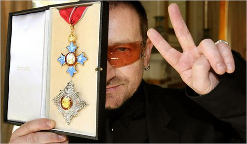 Bono showing off an award he received from Queen Elizabeth II...the same queen who have an award to mass abuser Jimmy Savile. Let's call this the occult elite award. And that's why Bono is hiding one eye with it.