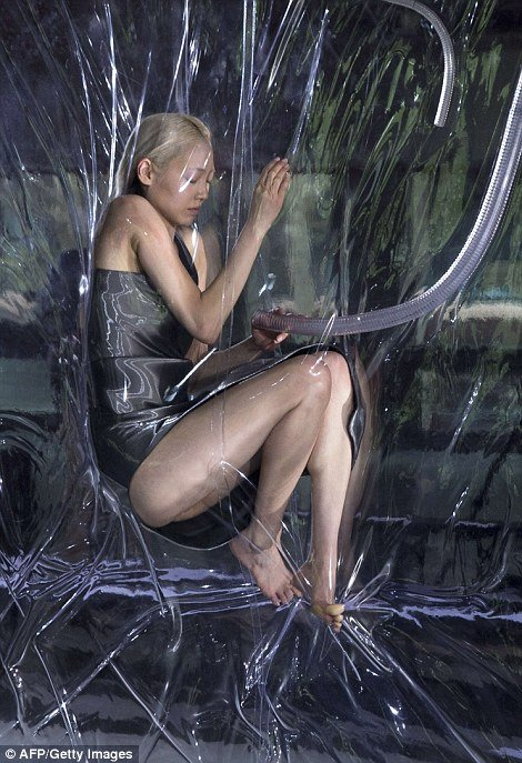 "One of Lady Gaga's favorite fashion designers, Iris van Herpen, launched her Fall 2014 fashion show in Paris. Called ""Biopiracy"", the show featured vacuumed packed models hanging next to the runway. While this display is said to ""raise questions"" about the patenting of genetics, what it mostly accomplishes is dehumanizing the models and comparing them to pieces of meat."