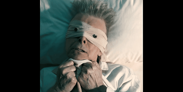 "In the role of the ""blind follower"", we see Bowie as the simple man, the regular human who is physical weak, laying on his deathbed and scared of things to come."