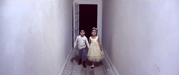 The children (who appear to be twins) walk creeplily backwards towards a black room.