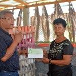 La presidenta de la Asociación Agropecuaria La Altagracia de Palo Alto, Barahona, Neida Ivelisse Pérez, recibe un cheque por la compra de la primera venta de carne de conejo, producida por esa agrupación.