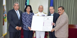El Almirante Sigfrido Aramis Pared Pérez, ministro de Defensa, recibe el reconocimiento de manos del presidente del Senado y su hermano, Reinaldo Pared Pérez y otros senadores.