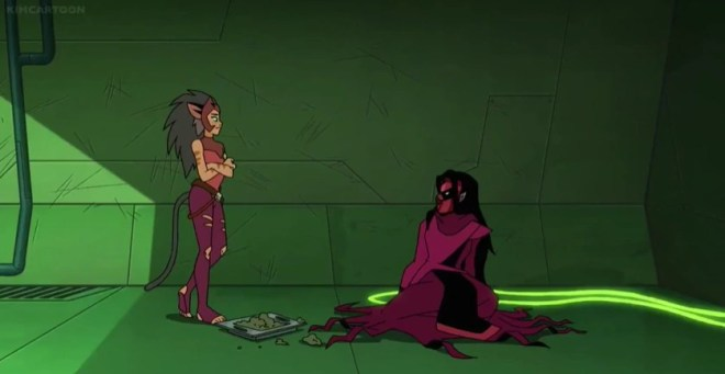 Catra, a young woman with feline traits, stands before Shadow Weaver, an older woman in an all-encompassing red cloak and dress wearing a red and black mask. Shadow Weaver is seated and her appearance is disheveled. She is shackled to the wall via long chains. Between them is a messy tray of nondescript food.