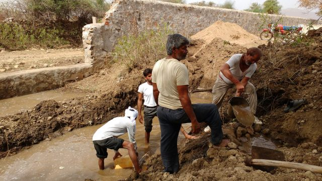 Gajanand Sharma (with bucket) builds an anicut on his farm to humour water.