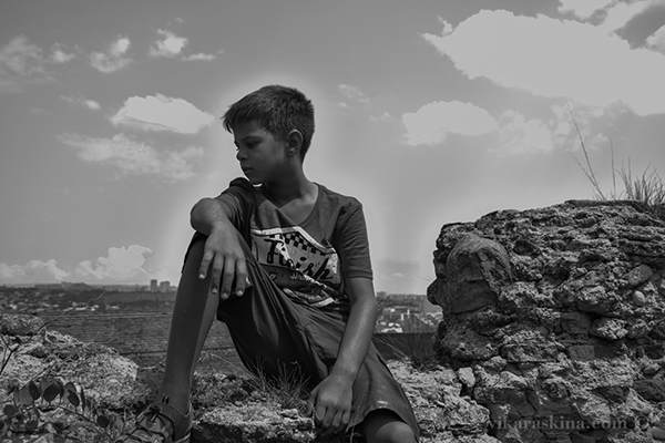 vika raskina - boy sitting on the stone