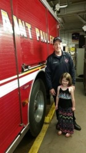 (Wolfsberger and his daughter at the Saint Paul fire station)