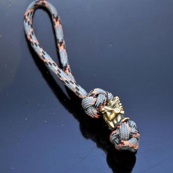 Фото плетеный из паракорда брелок с бусиной неандертаец
