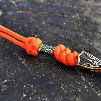 Фото оранжевый темляк из паракода для ножа с бусиной и трезубцем