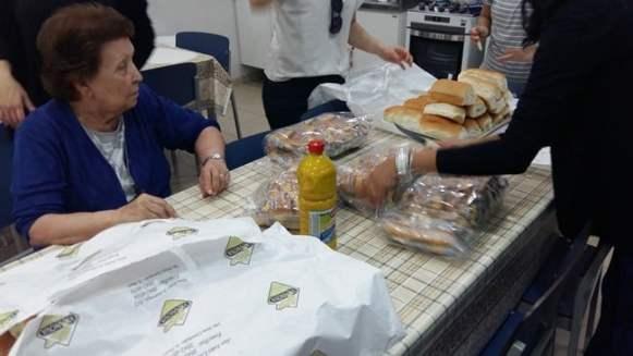 Irmãs, mães e funcionários no preparo dos pães de hot dog.