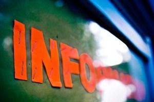 information écrit en lettre découpée dans du papier orange et agrafé sur un panneau