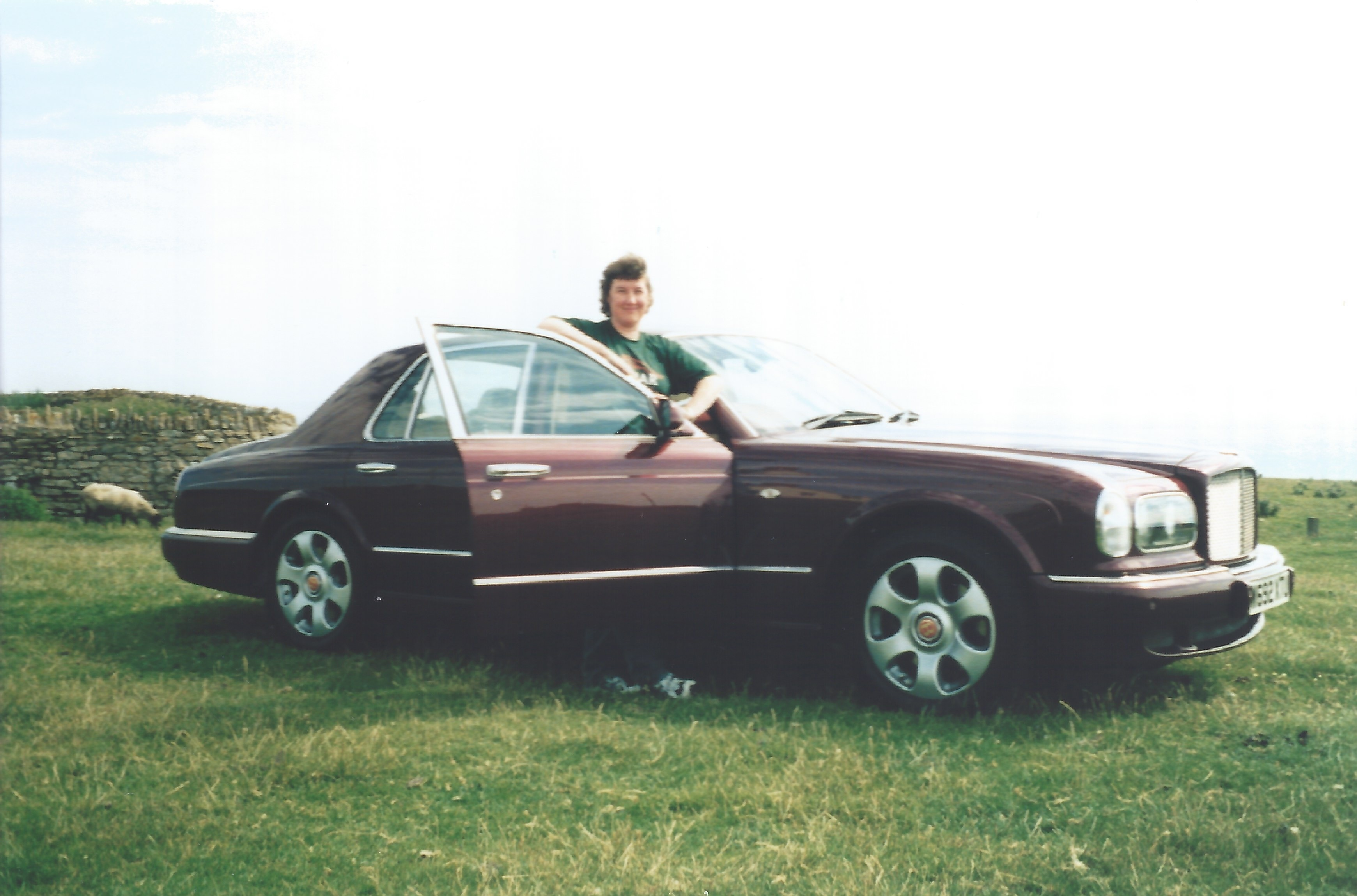 The author's wife stood ready to get in a dark mauve Bentley Arnage