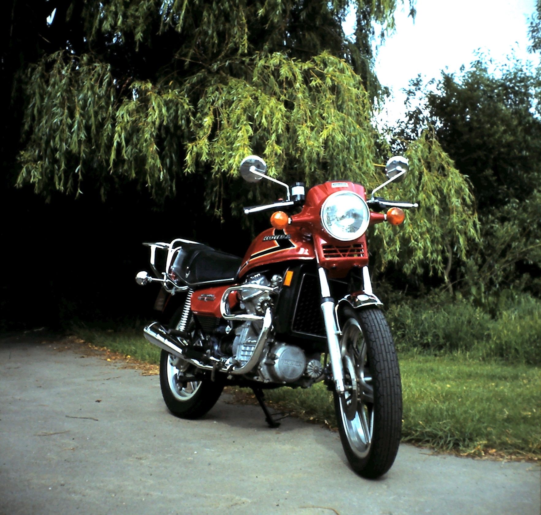 The front three-quarter view of a S-registration red Honda CX500, parked in the sunshine by a Willow tree