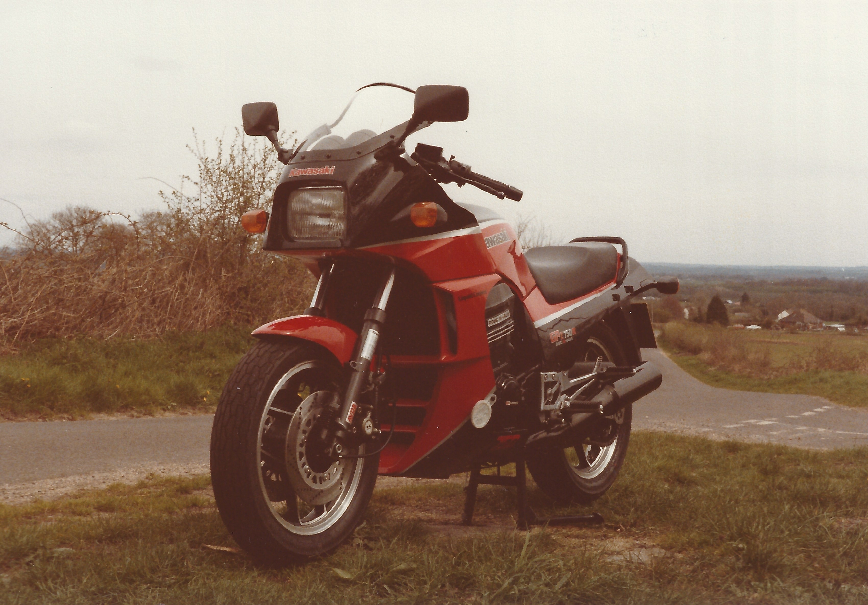 A black and red Kawasaki GPz750R motorcycle, which is stood on it's centre stand on a grass mound