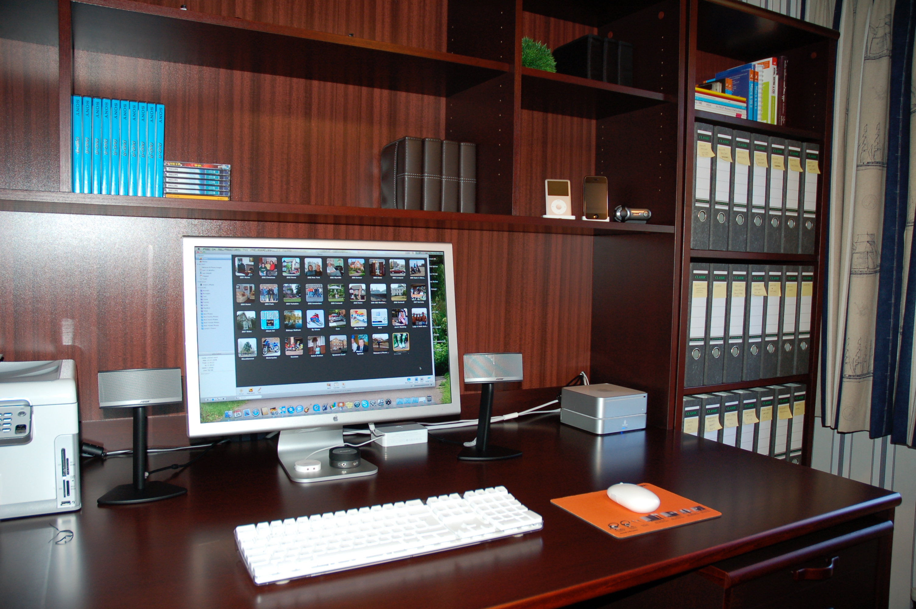 A MacMini on top of a matching back-up drive powers a 23 inch Mac monitor filled with photo icons, coupled to an optical mouse, printer and small stereo speakers, all on a dark wood desk unit with matching shelving and adjacent file system.  Files are in the filing system and an iPod Classic is on one of the shelves