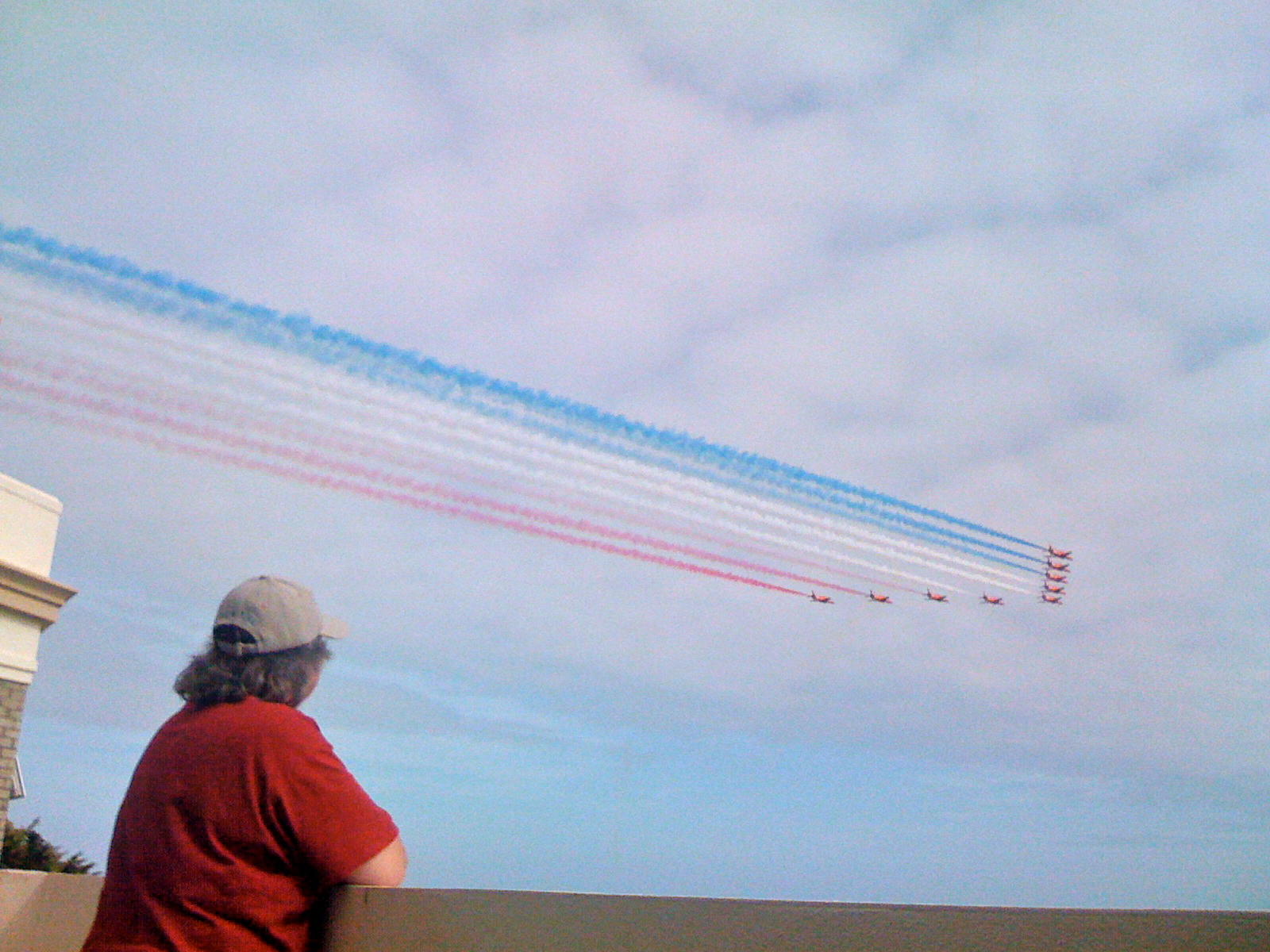 A photograph of the back of my wife in a red tee-shirt and beige cap stood on a balcony just as a nine plane Red Arrows jet formation flies past, trailing their blue, white and red smoke