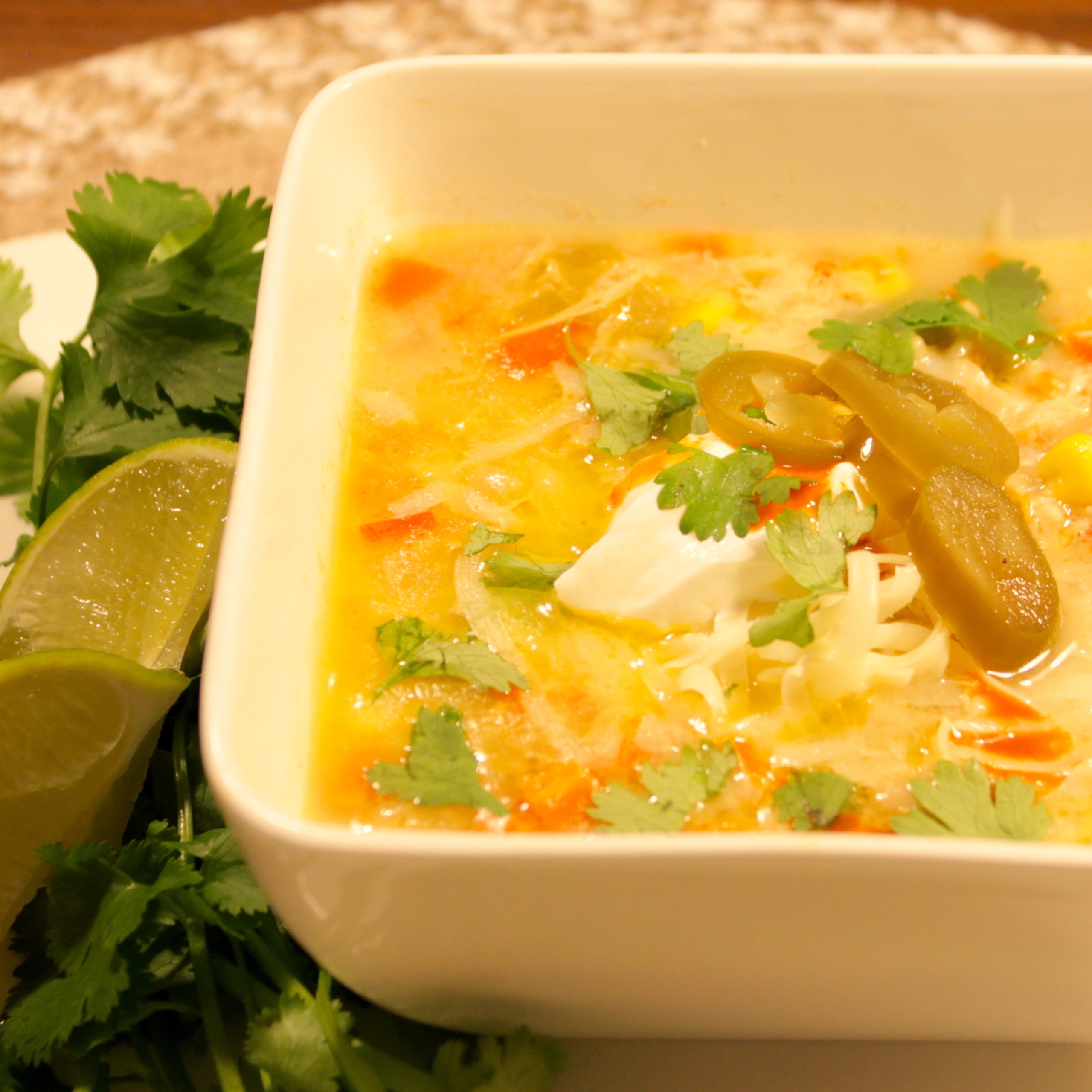 bowl of soup with cilantro and lime on side