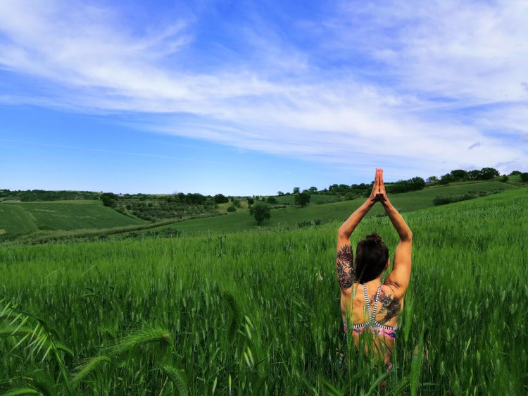 Yogavagabond doing Yoga in a field in Molise Italy