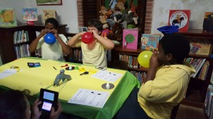 """File photo: Children create hovercrafts from balloons and CDs in a """"makerspace"""" at Sprauve Public Library PCC (March 2016)"""