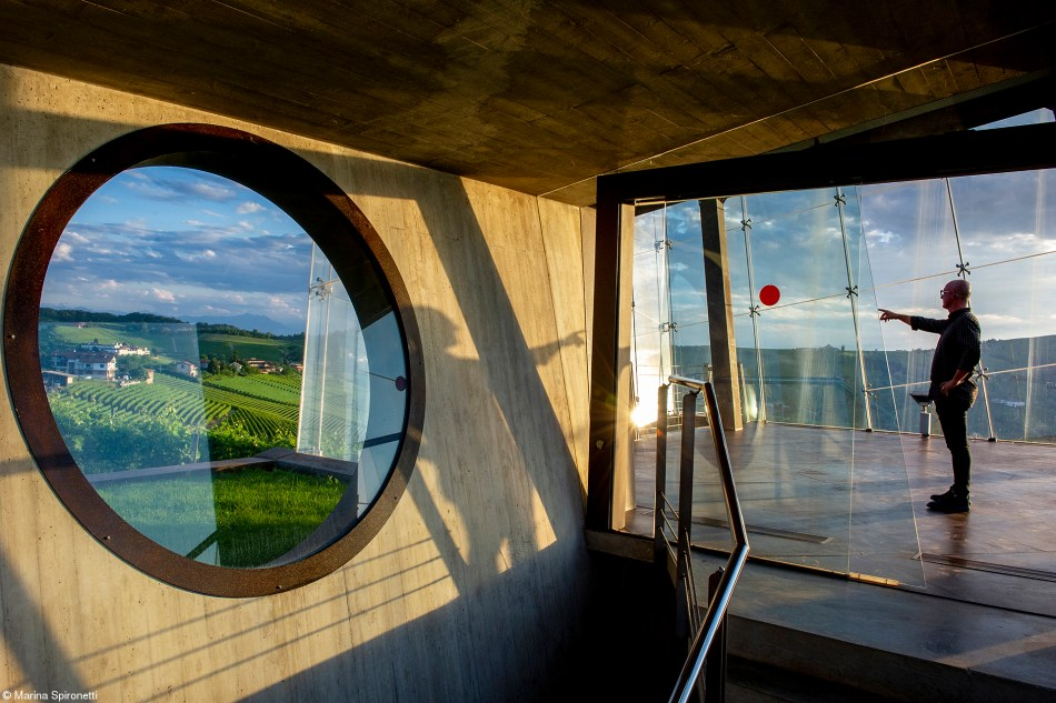 Inside the Cube Wine producer Federico Ceretto points something out inside the Cubo, the glass cube in the Bricco Rocche Estate, which is one of the landmarks of the Langhe region, Piedmont, Italy.
