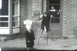 A still image from a film showing a family practicing on Stilts on Boxing Day 1954.