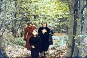 A still image from a vintage home movie made in 1958 showing a family taking a walk in the countryside.