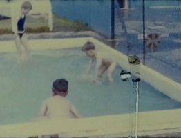A still image from a vintage home movie taken by a family enjoying a caravan holiday in the 1960s
