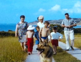 A still image from a vintage home movie showing a family on holday by the seaside