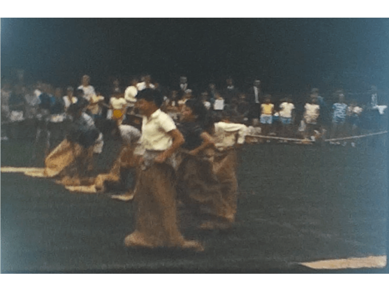 A still image from a vintage home movie showing Boys and Girls getting into sacks for the sack race
