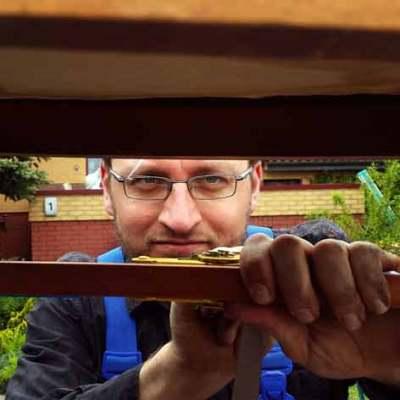 Robert Fiedler bei der Arbeit - frisch geleimter Stuhl wird mittels Spanngurten gepresst.