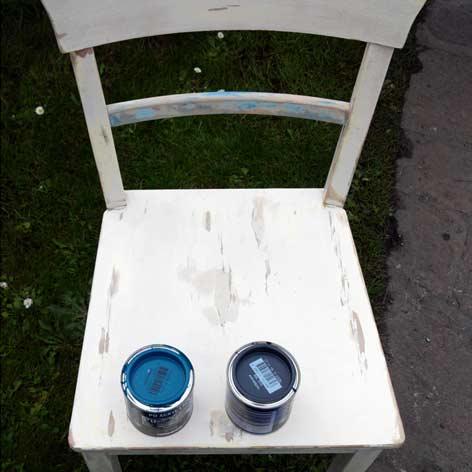 abgeschliffener Küchenstuhl mit zwei Farbtöpfen auf der Sitzfläche
