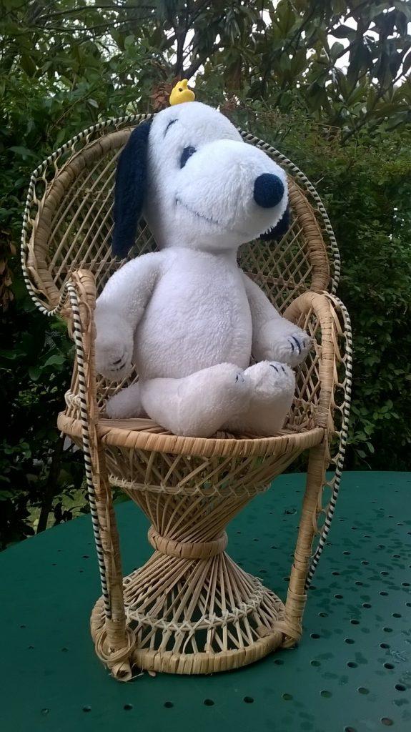 peluche Snoopy vintage dans un fauteuil en rotin style Emmanuelle