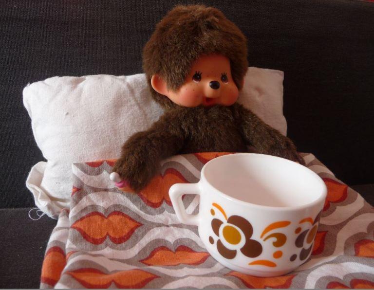 kiki dans son lit avec une tasse Arcopal à motif Knorr