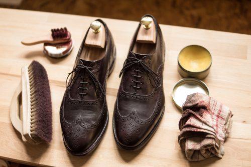 Ein paar rahmengenähter Full Brogues mit einigen Utensilien für die Schuhpflege