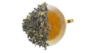 sweet milk oolong tea leaves displayed over a brewed cup of tea