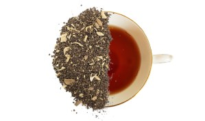 Decaf chai leaves overtop of a brewed cup of tea to show the tea product