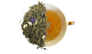 pineapple mango green tea leaves over a brewed cup of tea