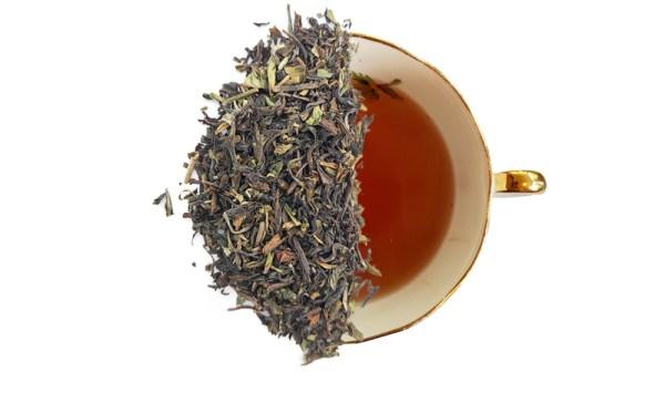 summer darjeeling tea leaves displayed over a cup of brewed tea