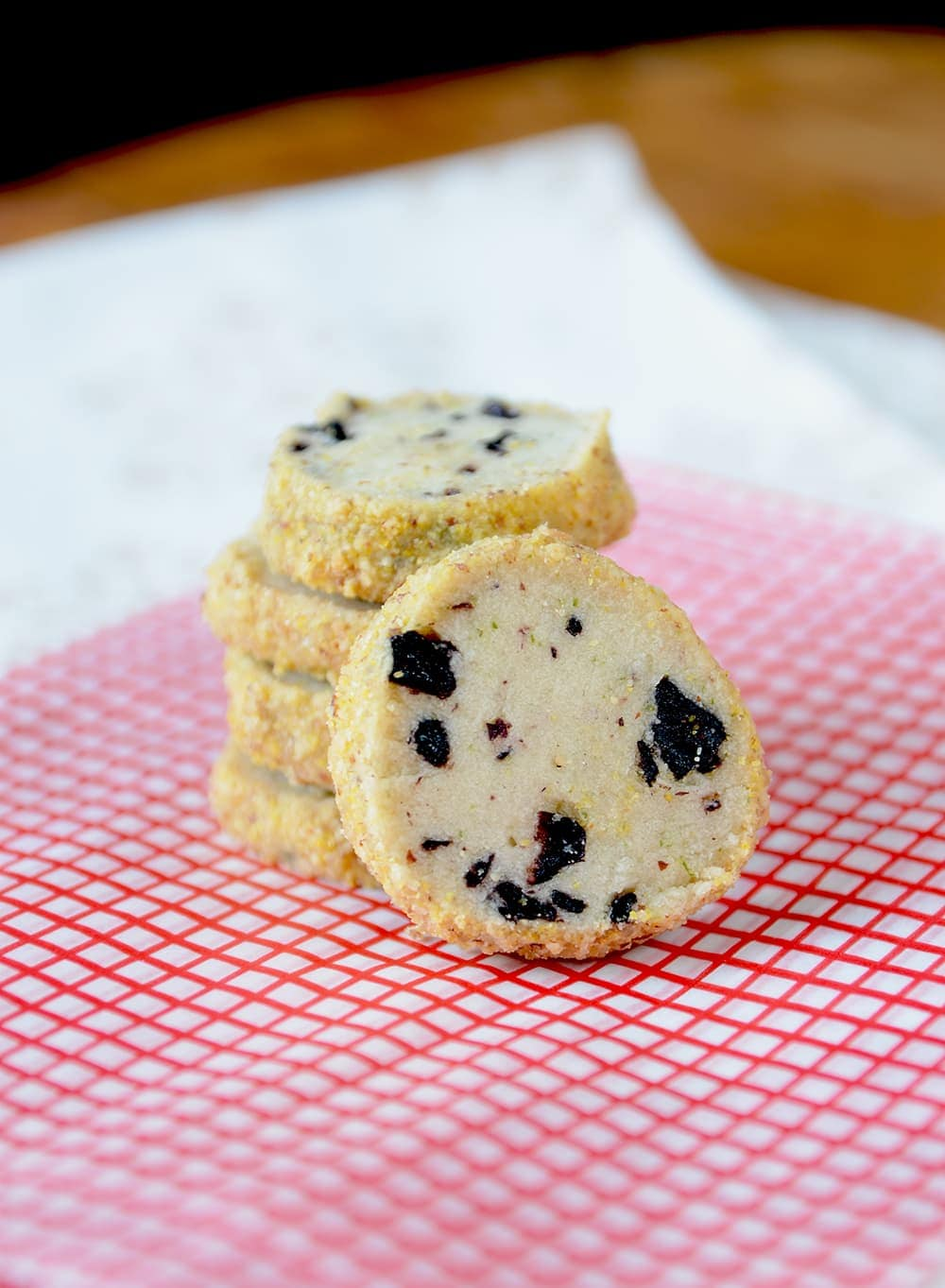 Blueberry Lime Shortbread is a great holiday icebox cookie. It's filled with dried blueberries and lime zest giving it a fresh, zippy flavor and coated in an almond cornmeal crumb for added texture and crunch.   vintagekitty.com