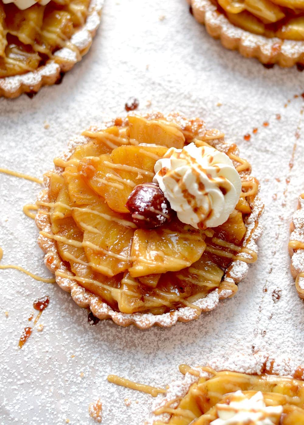 These Pineapple Rum Tartlets pack a punch of flavor! Fresh pineapple gets drenched in a sugary, rum concoction and layered into a sweet and crumbly crust. The pineapple itself is a symbol of welcome and hospitality, so perfect to serve guests for holidays or special dinners. | vintagekitty.com