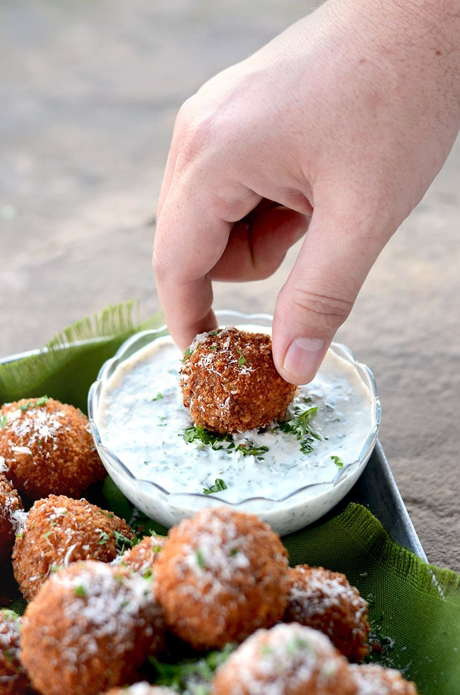 Fried Mozzarella Balls with Pumpkin, Sage + Caramelized Onion are the perfect holiday appetizer! Crunchy, gooey, deliciousness served with Yogurt Herb Dip.