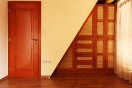 Porta de madeira, armário embutido de madeira e pavimento de madeira.