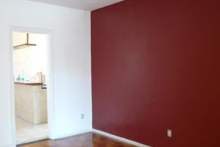 Pintura em sala com paredes branca e vermelha.