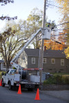 Picture of a boom truck with a technician pulling fiber on an existing utility pole line for Google.