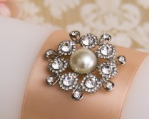 Wedding candle with a rhinestone and crystal brooch with a large pearl in the center.