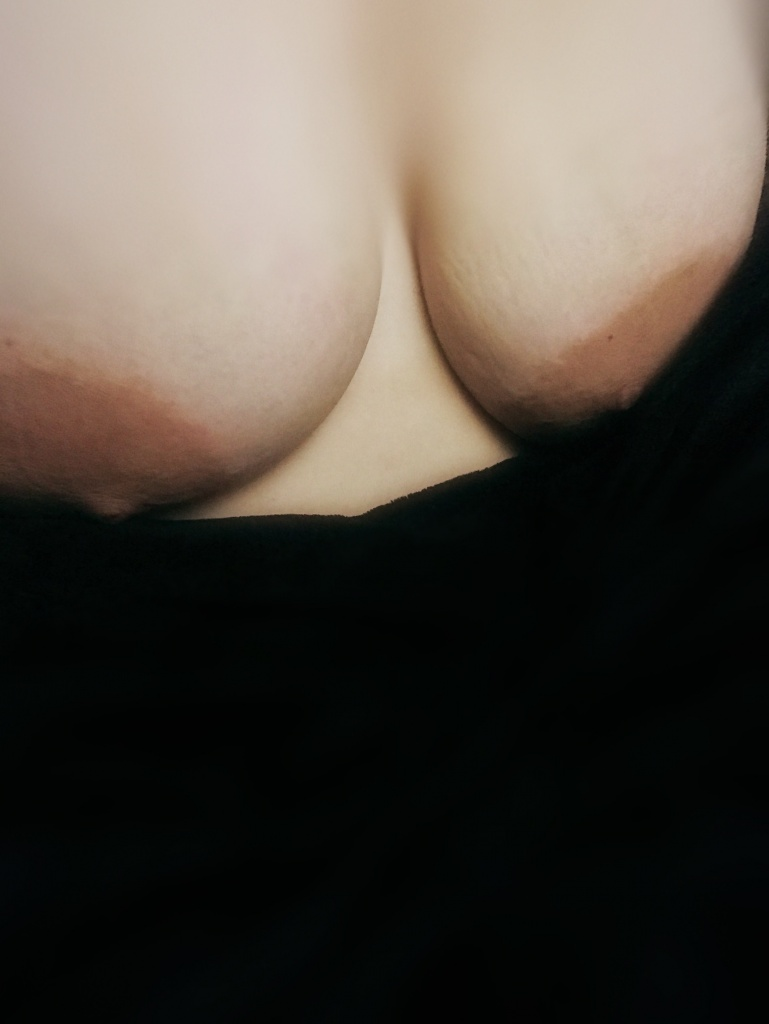 Caucasian woman's breasts exposed against black velvet blanket